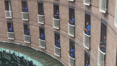 Rugby team singing from individual hotel balconies