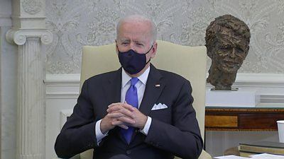 President Biden sitting down and wearing a black face mask.