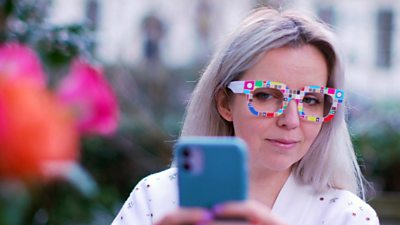 BBC Click reporter Jen Copestake wears a pair of Zozoglass and holds a smartphone