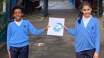 Children holding new school emblem