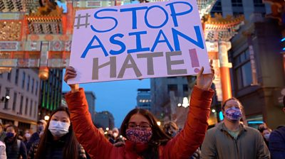Woman holding sign reading 'stop Asian hate'