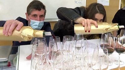 A man and a woman pour two bottles of wine into glasses - one bottle has been into space