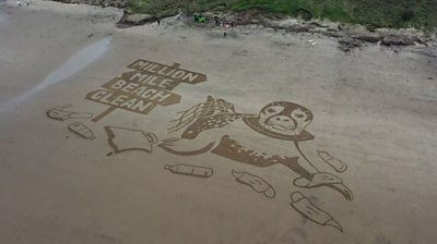 Sand drawing of seal surrounded by litter