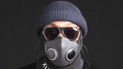 Artist will.i.am wears a blue beanie hat, sunglasses and the Xupermask - a smart facemask