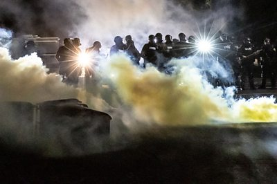 Police officers amid tear gas during protest