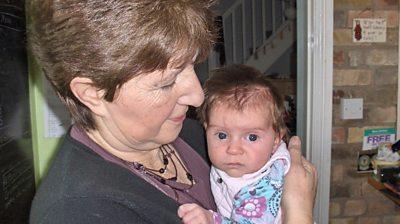 Jude Stewart holding a baby