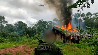 IBAMA officer in front of burning building