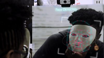 A scene from Coded Bias where Joy Buolamwini holds a white mask in front a
