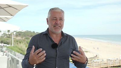 Man in shirt standing in front of a beach