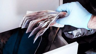 A gloved hand holds UK bank notes