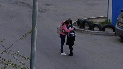 A parent hugs her child after deadly Kazan shooting