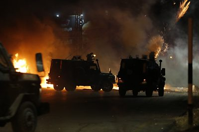 Police forces in cars fire tear gas