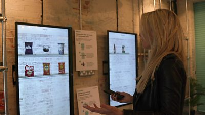 Lara Lewington stands in front of touch screens displaying a range of products