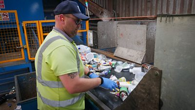 A man sorting recycling on a conveyor belt