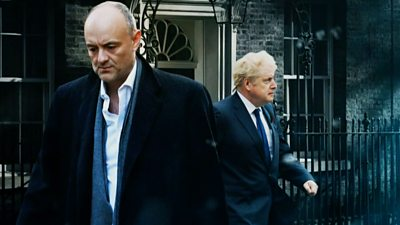 Dominic Cummings outside Downing Street with Prime Minister Boris Johnson behind him walking to the right.