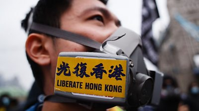 Protester wearing gas mask with 'Liberate HK' sticker