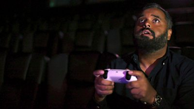 Click reporter Marc Cieslak holds a gaming controller while playing a game on a cinema screen