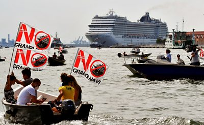 Protesters in a boat in front of the cruise ship, with signs that read 'no big ships.'