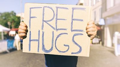 Person holds up free hugs sign