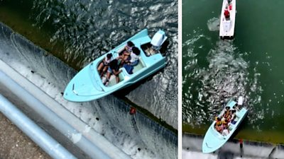 The four passengers were rescued after their boat got stuck at the top of the dam.