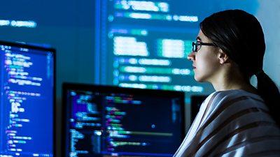woman looking at computer monitors