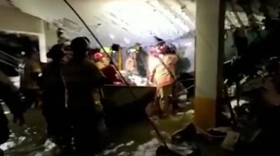 firefighters search through rubble