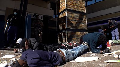Men lying face-down in front of building