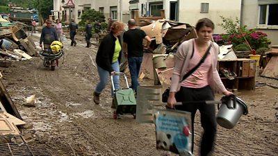 People with belongings walking on muddy road