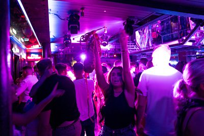A woman dances on the first night clubs reopen in England