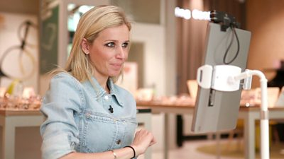 BBC Click's Lara Lewington looking at screen after having her face 3D scanned, behind her are glasses