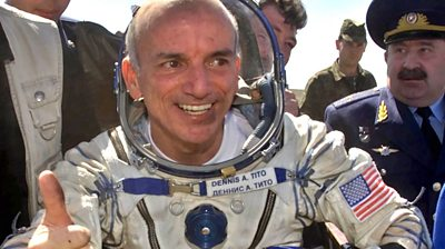 Dennis Tito in a space suit giving a thumb's up