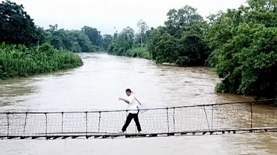 Health worker walking along a rope bridge across a jungle river