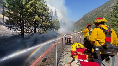 Firefighters spray water from a train roof