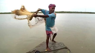 Man casts net out into water