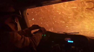 As burning ash pelts their vehicle, video shows firefighters in California drive through the flames.