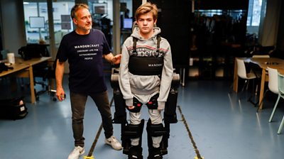 Father and son in robotic suit