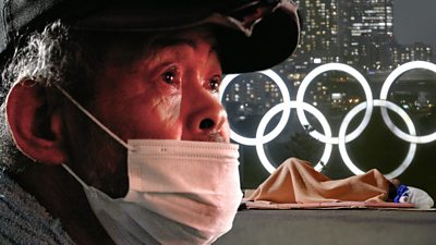 Homeless man in front of Olympic rings