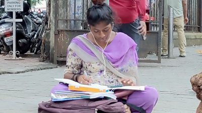 17-year-old Asma studies on a foothpath in India's Mumbai city.