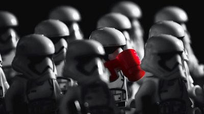 A stormtrooper drinks a coffee