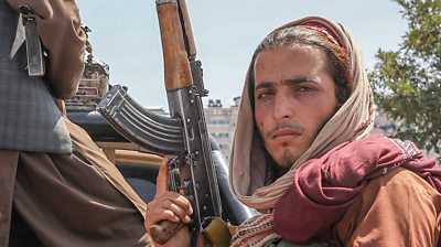 Taliban fighter sits in a vehicle in Kabul