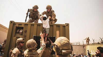 UK coalition forces, Turkish coalition forces, and US Marines assist a child