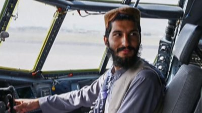 Taliban fighter poses in the cockpit of aircraft