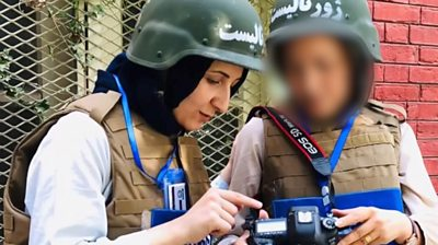Wahida and a colleague wearing a helmet looking at a camera