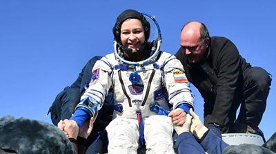 Yulia Peresild is helped after landing in Kazakhstan