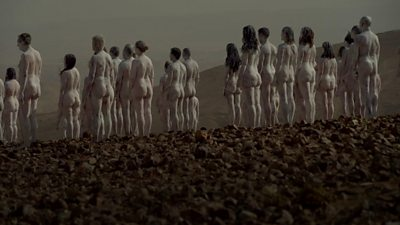 Naked people painted white and stood near the Dead Sea