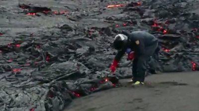 Scientist collecting lava sample