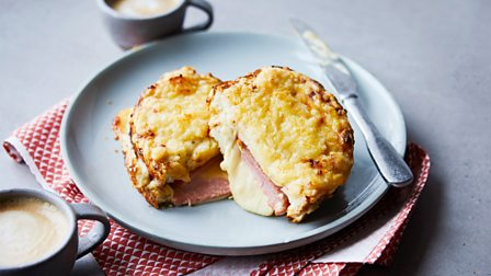 Croque monsieur cut in half on a plate with a knife next to it and a coffee cup in front