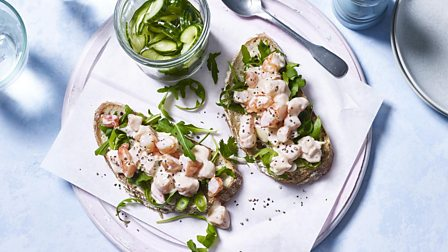 An open sandwich with rocket, prawns and a side dish of pickled cucumbers
