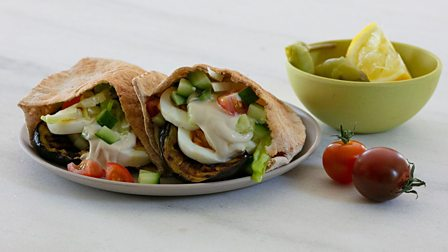 A Sabich sandwich served with a side of pickles and garnished with cherry tomatoes