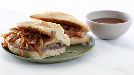 A French dip sandwich with a side of gravy
